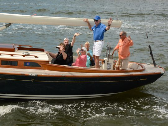 VIPs wave as they head out of Naples Bay for the Sailing Heals event